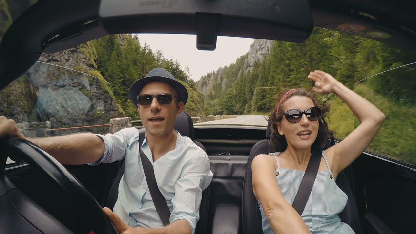 4K video: happy couple sings the songs while the roofless convertible car driving by the mountain road.