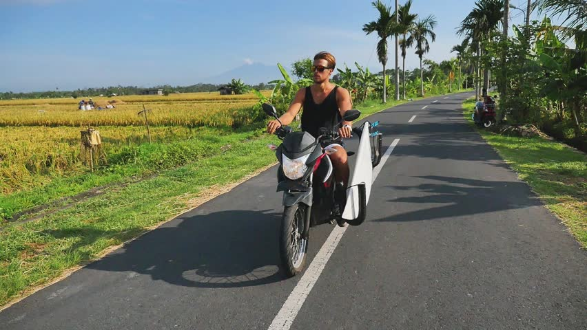Man riding a motorcycle with surfboard by the road near beautiful rice terraces, Indonesian activity culture. Handsome man gonna to surf spot. Surfing lifestyle adventure | Shutterstock HD Video #1006952041