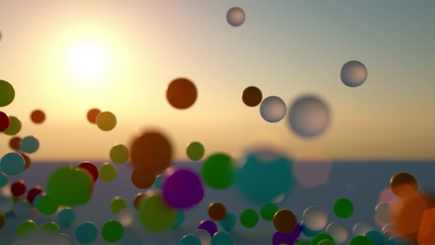 colorful bouncing rubber balls outdoors against clear sunset sky - shot in slow motion