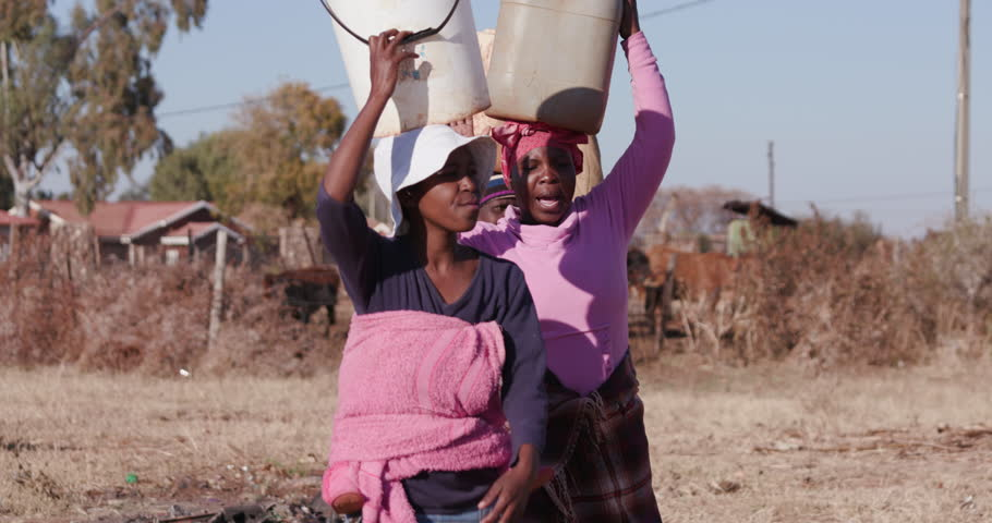 Poor people in Africa unable to maintain social distancing due to water crisis. The plight for fresh water.Three african woman carrying water on their heads in plastic buckets. Royalty-Free Stock Footage #1006974166