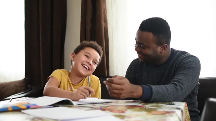 Mixed family at home. African father and african american child. dad helping son with school homework. Education and relationship, man teaching and boy learning. home schooling.  Royalty-Free Stock Footage #1006992934