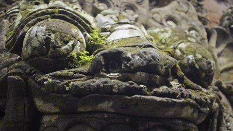 Balinese ancient religion statue big head rakasa covered moss, close-up slider motion shot