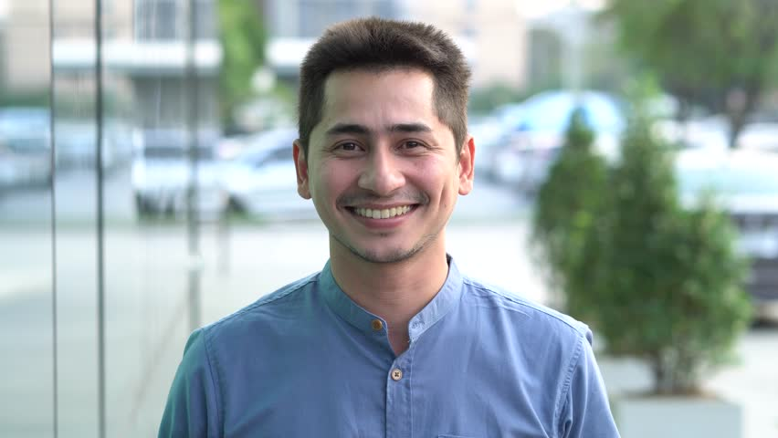 Young man asian smiling and looking at camera. Portrait of a happy handsome young man in a urban street. Close up face of young cool trendy man looking at camera | Shutterstock HD Video #1007011720