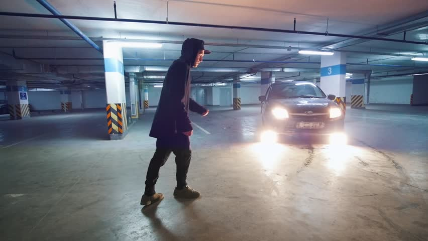 Slow-motion shot of acrobatic guy performs tricks at underground parking #1007016994