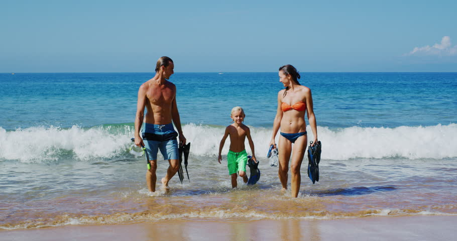 Young family walking out of the ocean with snorkel gear on vacation