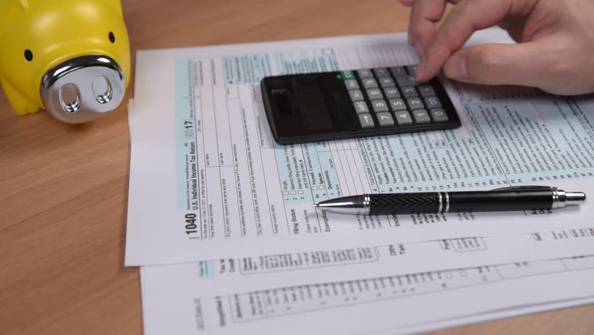 Tax form 1040, pen, Piggy bank and calculator. on the desk. Royalty-Free Stock Footage #1007028808