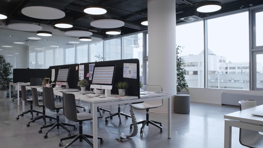 Tracking shot of empty open space office with stylish interior, panoramic window, comfortable furniture and modern computers
