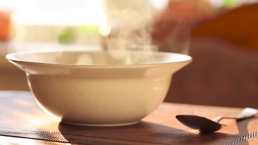Hot soup in a plate, steam rises above a white ceramic plate, next to it lies a spoon