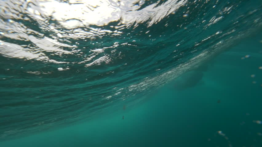 UNDERWATER SLOW MOTION Enormous wave breaking creates foam and countless air bubbles fill space under ocean surface. Glass like sea level glistens from sun lighting up the depths darkened with waves