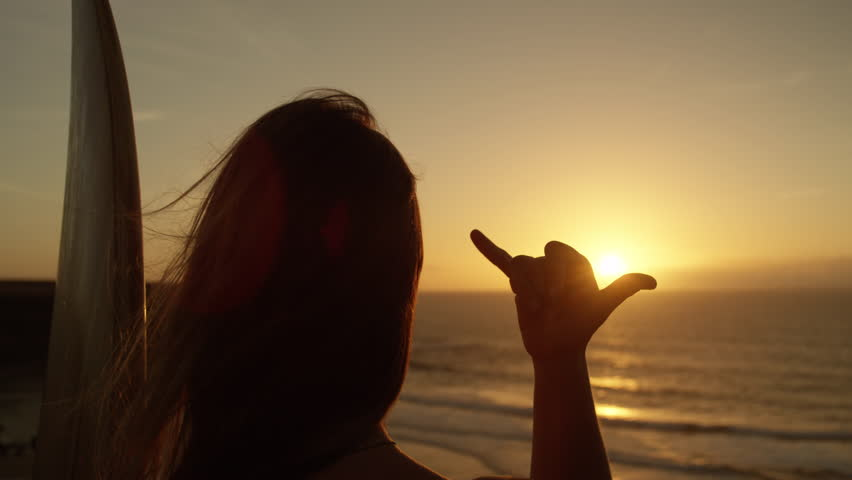 SLOW MOTION CLOSE UP: Unrecognizable girl with long flowing hair gazing at golden sunset giving the shaka sign. Female surfer making hang loose signal with her hand. Woman using Hawaiian hand gesture | Shutterstock HD Video #1007042920
