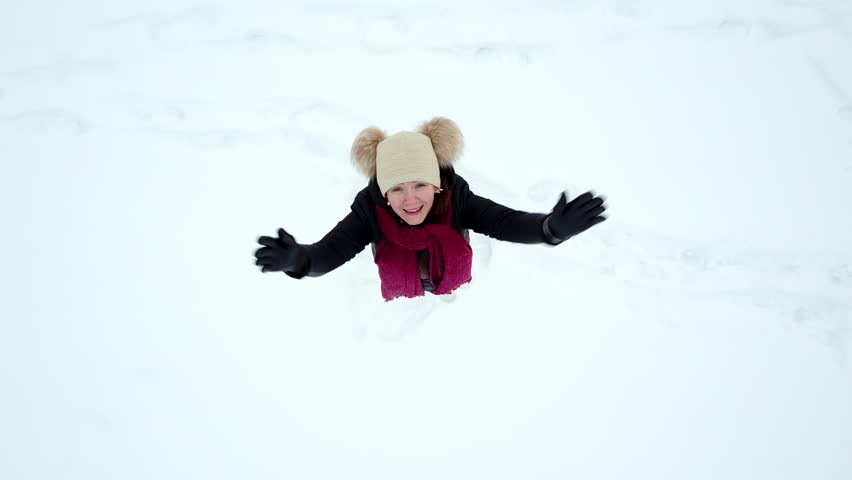 Young cheerful woman stay on snow field, look up and spin around, top-down aerial dronie shot, camera fly up while looking straight down and rotate. Girl smile and whirl, lie down and make snow angel | Shutterstock HD Video #1007048413