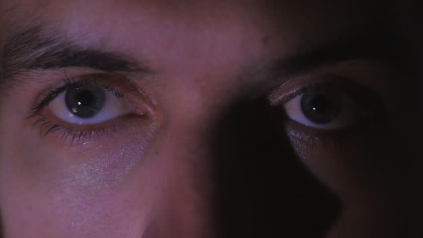 Close up eyes of a young man watching a video or film on TV or a computer monitor. Reflection on her face | Shutterstock HD Video #1007048590