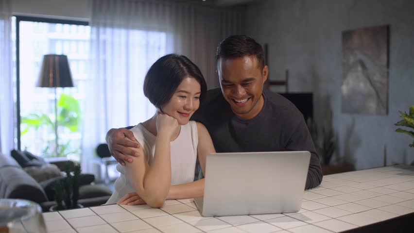 Happy Asian couple looking at the computer together at home. Royalty-Free Stock Footage #1007048923