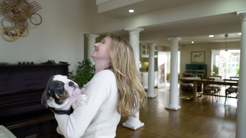 Young woman dancing with her dog in a living room
