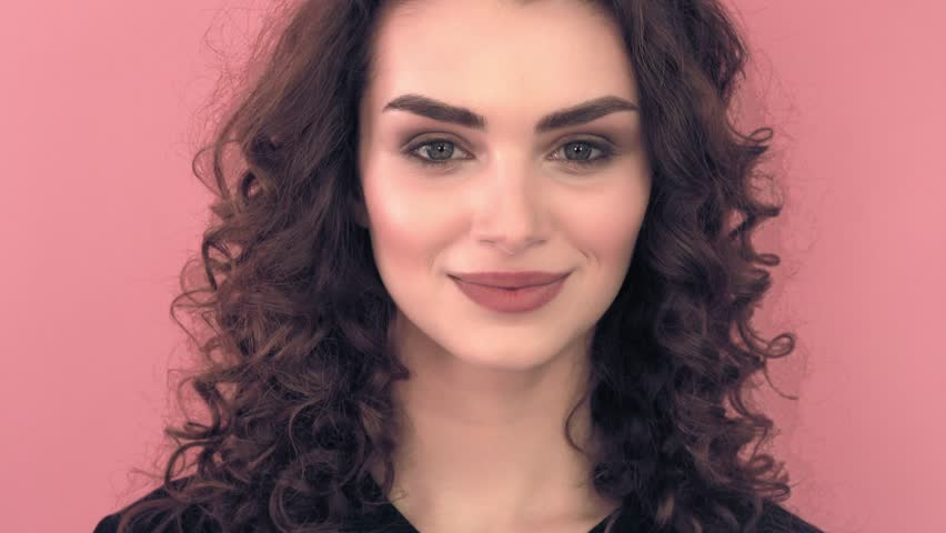 Beautiful fashionable girl with long curly hair and snow-white smile in a black T-shirt. Girl in the studio on a pink background.Advertising, hair products, beauty salon, cosmetics, clothing