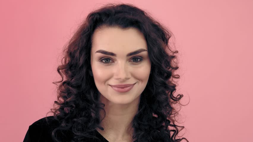 Beautiful fashionable girl with long curly hair in a black T-shirt. Girl in the studio on a pink background.Advertising, hair products, beauty salon, cosmetics, clothing. Fashion, boutique. Pink.
