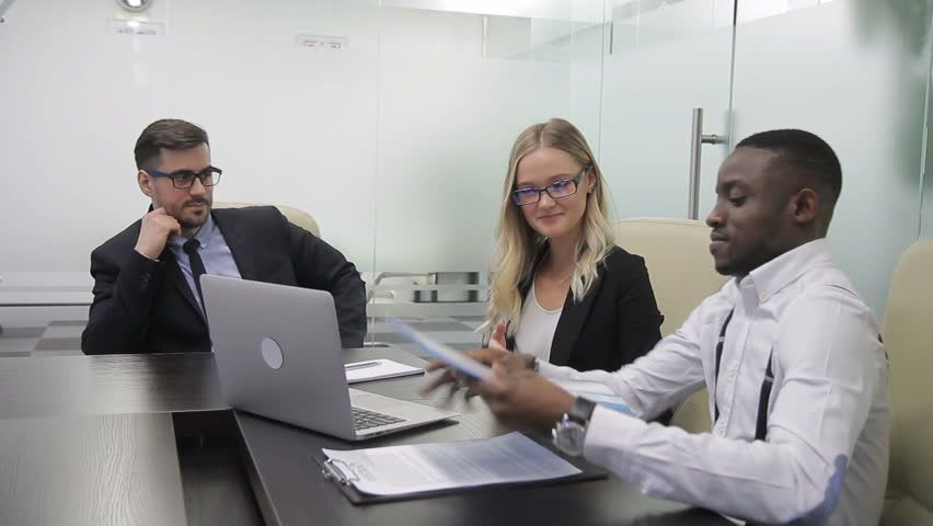 Multi-ethnic managers are presenting their financial report to their boss in the office. Blond woman, african man are giving the folder with documents to the businessman in suit and glasses, who is | Shutterstock HD Video #1007065735