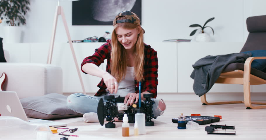 Young attractive teen girl assembling toy RC car at home, modern interior. Hobby concept. 4K UHD | Shutterstock HD Video #1007067526