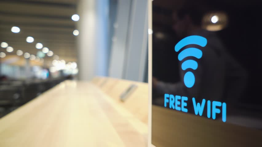 young man uses a phone on a background of a Free Wifi Signal Sign flashes on display in a cafe Royalty-Free Stock Footage #1007072461