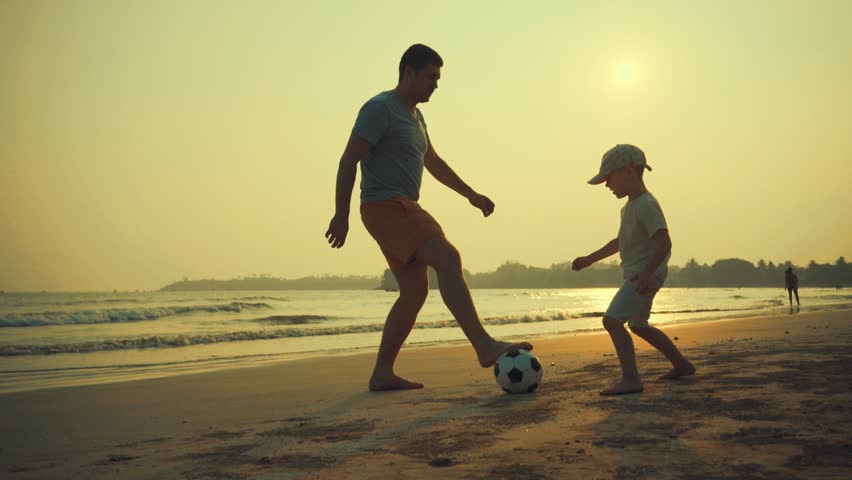 Father and son playing together with ball in football on the beach under sunset background #1007073166