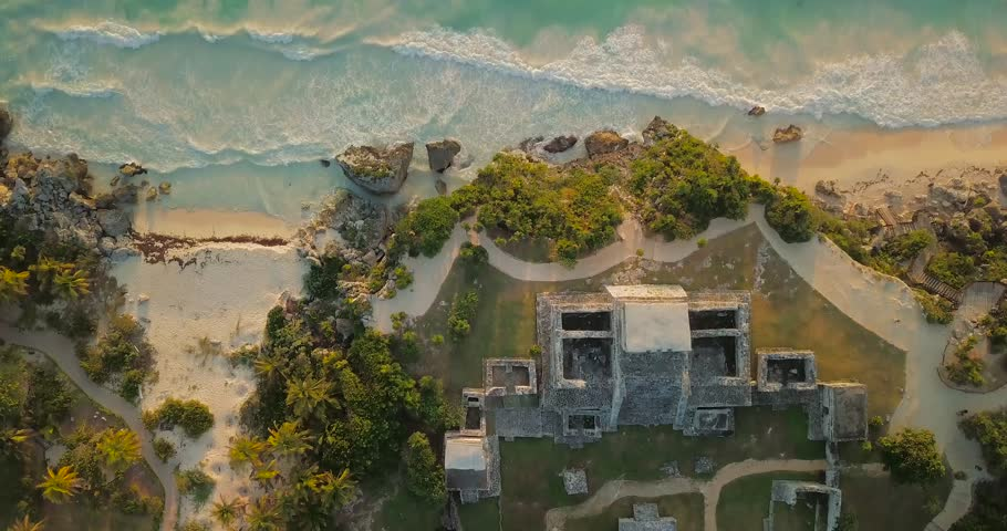 Birds eye and tilt view from Mayan temple Ruin drone sky shot over sea with waves in Tulum Mexico at sunrise