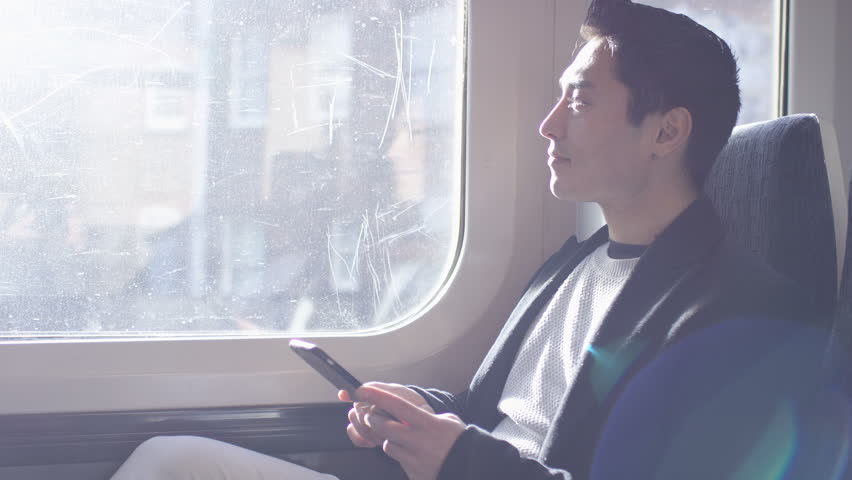Confident man on a train journey using his phone, in slow motion | Shutterstock HD Video #1007079562