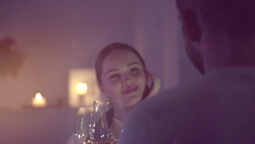 Romantic dinner. Young couple drinking Wine and holding hands restaurant or at home. Proposing, Dating. Beautiful brunette woman on romantic dinner, Date. Valentine Day celebrating. 4K UHD Slow motion
