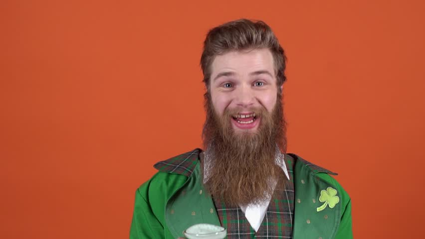 Young man leprechaun celebrating saint patrick's day isolated on orange wall offering green beer