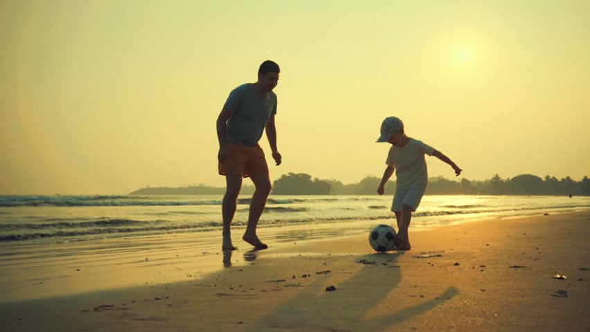 Father and son playing together with ball in football on the beach under sunset background #1007097430