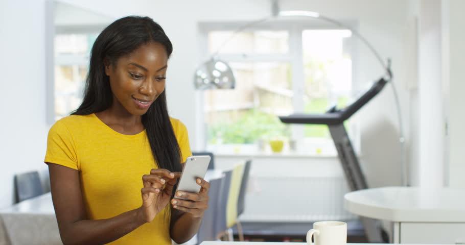 4K Young African American woman in modern home texting on smartphone | Shutterstock HD Video #1007098918