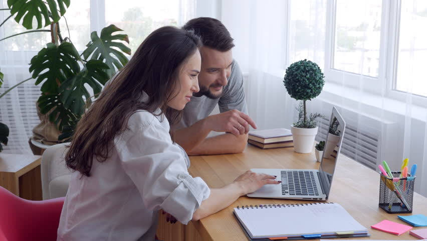 Couple looking at the laptop and choosing something   Shutterstock HD Video #1007099638