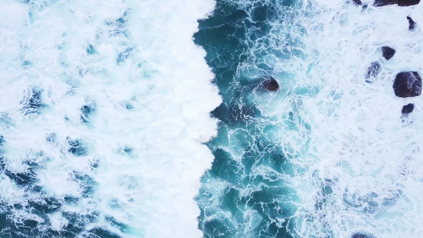 Top view moving up away ocean blue waves crash coastline cliff drone footage