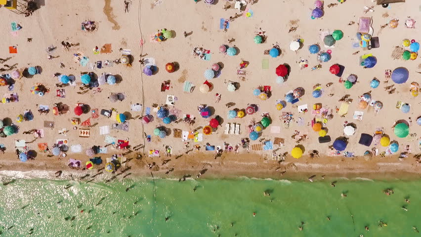 Aerial view of the beach filled with people on a hot sunny day. Sun umbrellas stand in yellow bright sand. People rest and sunbathe on the beach on a summer day near the ocean. | Shutterstock HD Video #1007123050