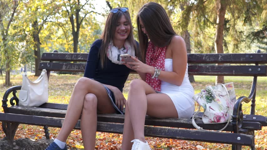 SLOW MOTION: Attractive girls looking at phone and laughing on bench | Shutterstock HD Video #1007130685