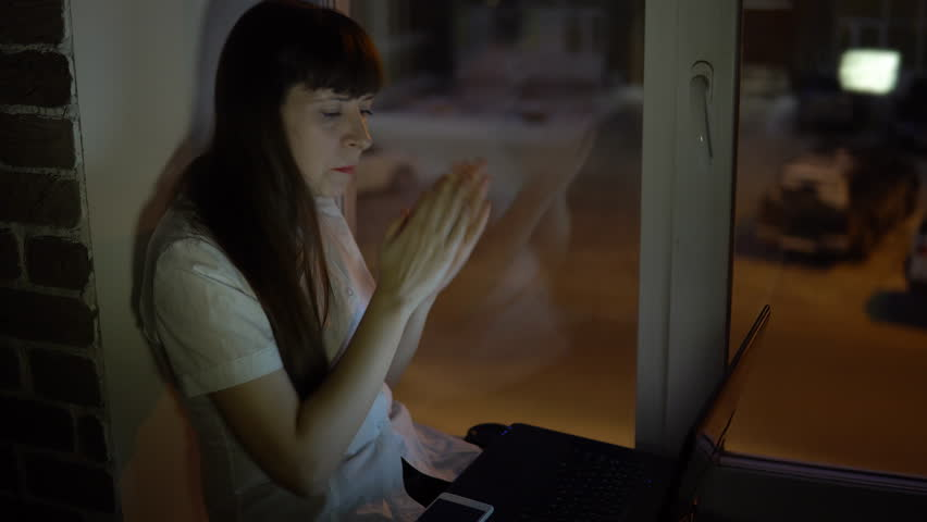 A business woman is sitting on the windowsill and and applauds in front of the laptop during a video conference evening, outside the window in the street a road with a busy traffic. | Shutterstock HD Video #1007132671