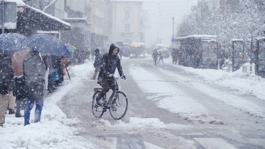 LJUBLJANA, SLOVENIA - JANUARY 2018: Person bicycling in city snow blizzard slow motion 4K. Wide view of Ljubljana city center road with a single bicyclist in focus driving over the dangerous road. Royalty-Free Stock Footage #1007141656