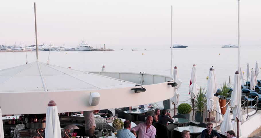 France, Cannes, 27 May 2017: Embankment of Cannes at the cinema Cannes Film festival the Palm branch at sunset, beach cafes, umbrellas, crowded cafes, pink sky #1007148622