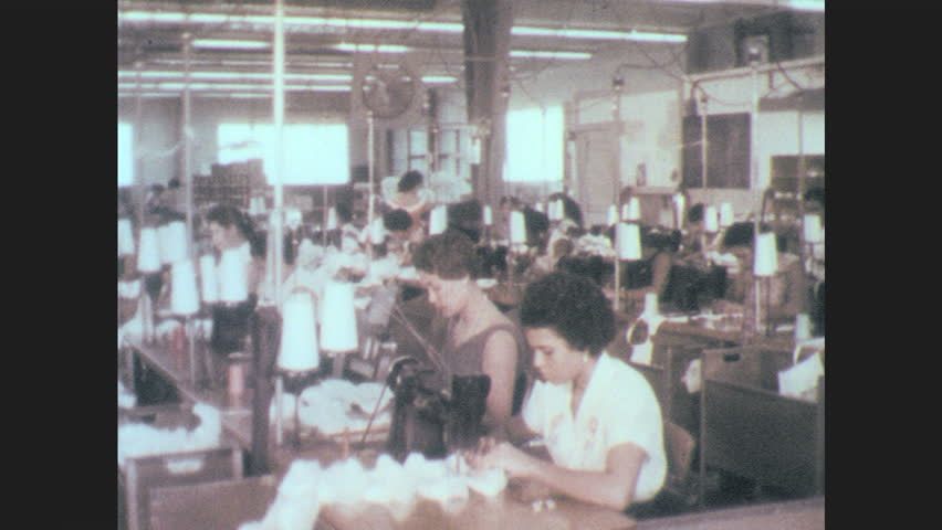 Puerto Rico 1960s: Women work on sewing machines in clothing plant. Cars and buses drive by government building. | Shutterstock HD Video #1007157940
