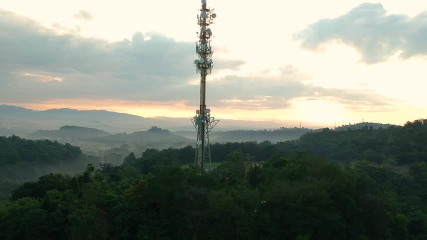Aerial footage of Communication tower during morning sunrise with clouds, mists and fog #1007162734