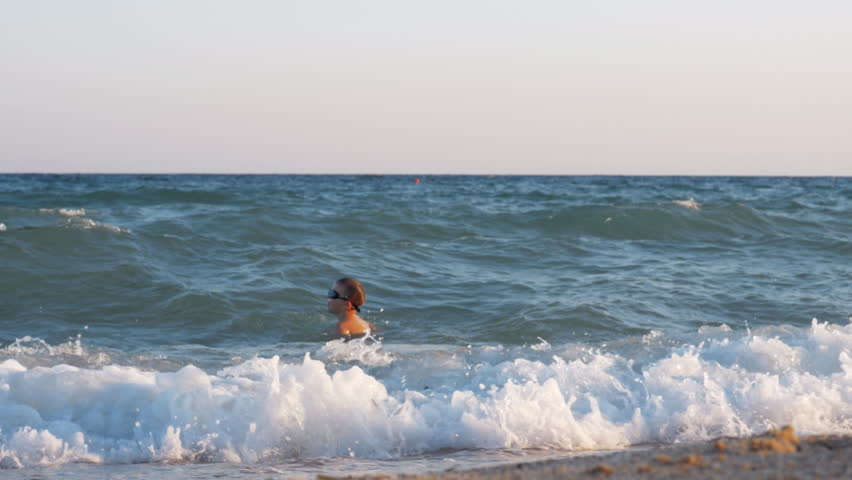 Slow motion shot of a happy boy in goggles swimming in the sea. He is excited with waves which rolling in and crushing the beach with high splashes   Shutterstock HD Video #1007175766