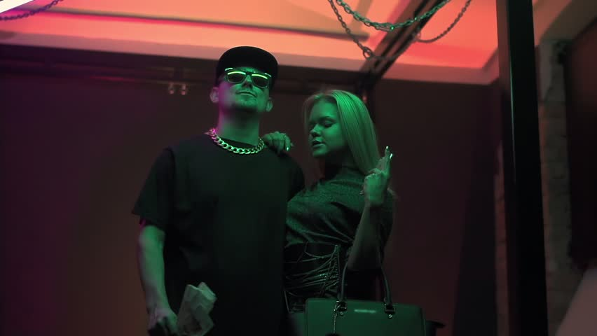 Hip hop caucasian man in sunglasses and spiked cap throws money with sexy girl in expensive clothes at colorful light studio