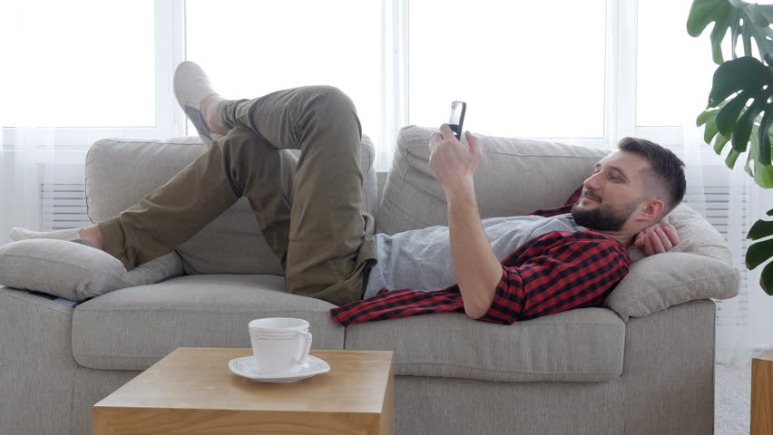 Bearded man reading message on the phone in the sofa | Shutterstock HD Video #1007183326