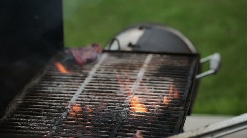 man puts meat steaks on the grill