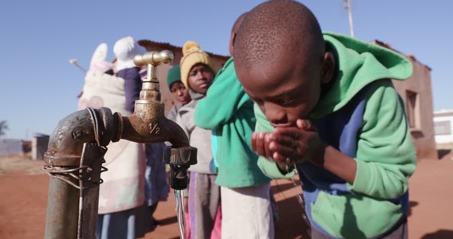 Poor people in Africa unable to maintain social distance due to water crisis. Young african boys drinking water from a tap while woman line up to collect water in plastic containers