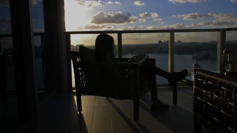 Silhouette woman, reads book on condominium patio at sunrise, tracking shot.
