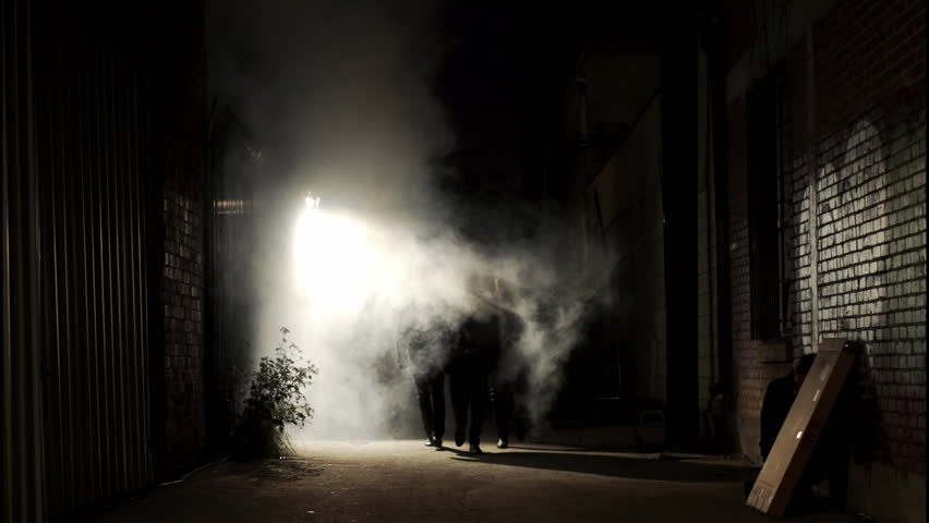 Wide shot of a silhouetted group of three men walking down a dark alley at night, passing through a backlit cloud of steam. Royalty-Free Stock Footage #1007199352