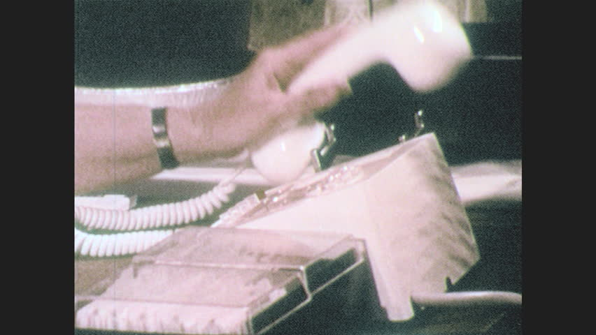 1960s: UNITED STATES: hand picks up phone. Lady speaks on phone. Lady in meeting. View across Sheraton hotel building