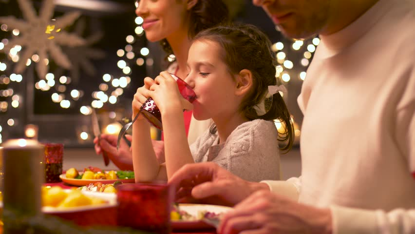 holidays, family and celebration concept - happy mother, father and little daughter having christmas dinner at home #1007240602