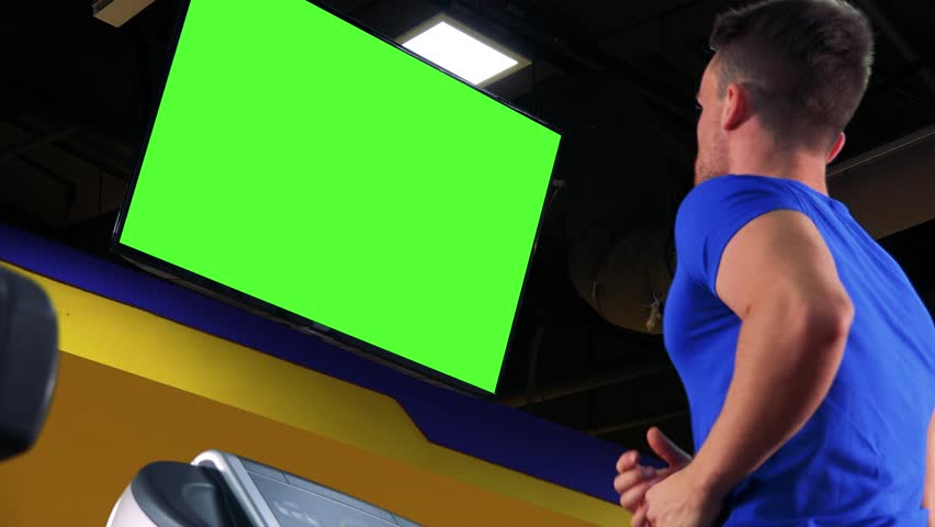 A young fit man jogs on a treadmill in a gym and watches a green screen - view from below