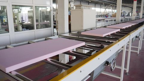 mechanized process production of building material from foam plastic at plant, close-up